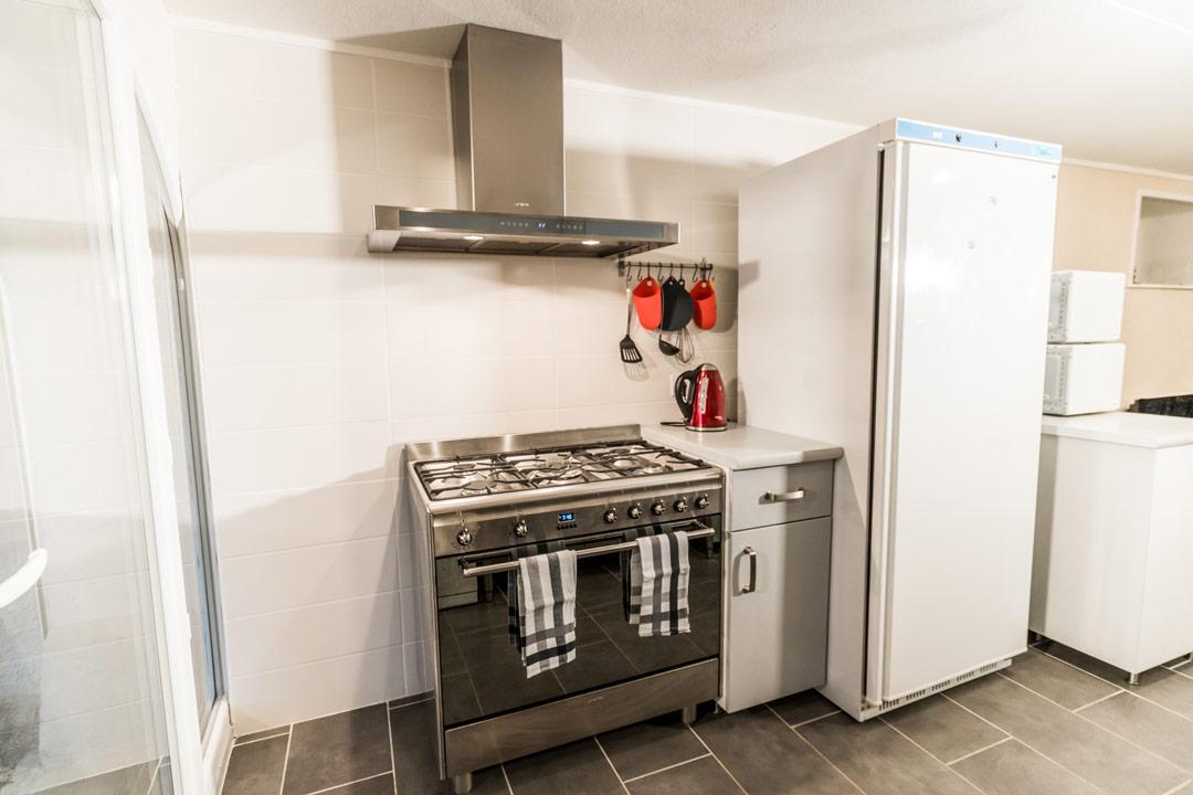 Salle commune pouvant accueillir jusqu'à 24 personnes avec cuisine professionnelle, lave vaisselle, plaques de cuisson, parfait pour vacances en hiver dans le Jura en famille ou entre amis - Gites les Gentianes