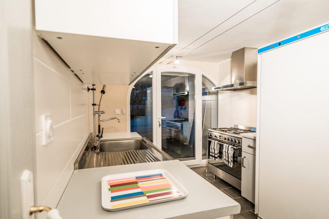 Salle commune avec cuisine professionnelle, lave vaisselle, plaques de cuisson, évier pro, idéal pour cousinades ou repas de famille - Gites les Gentianes